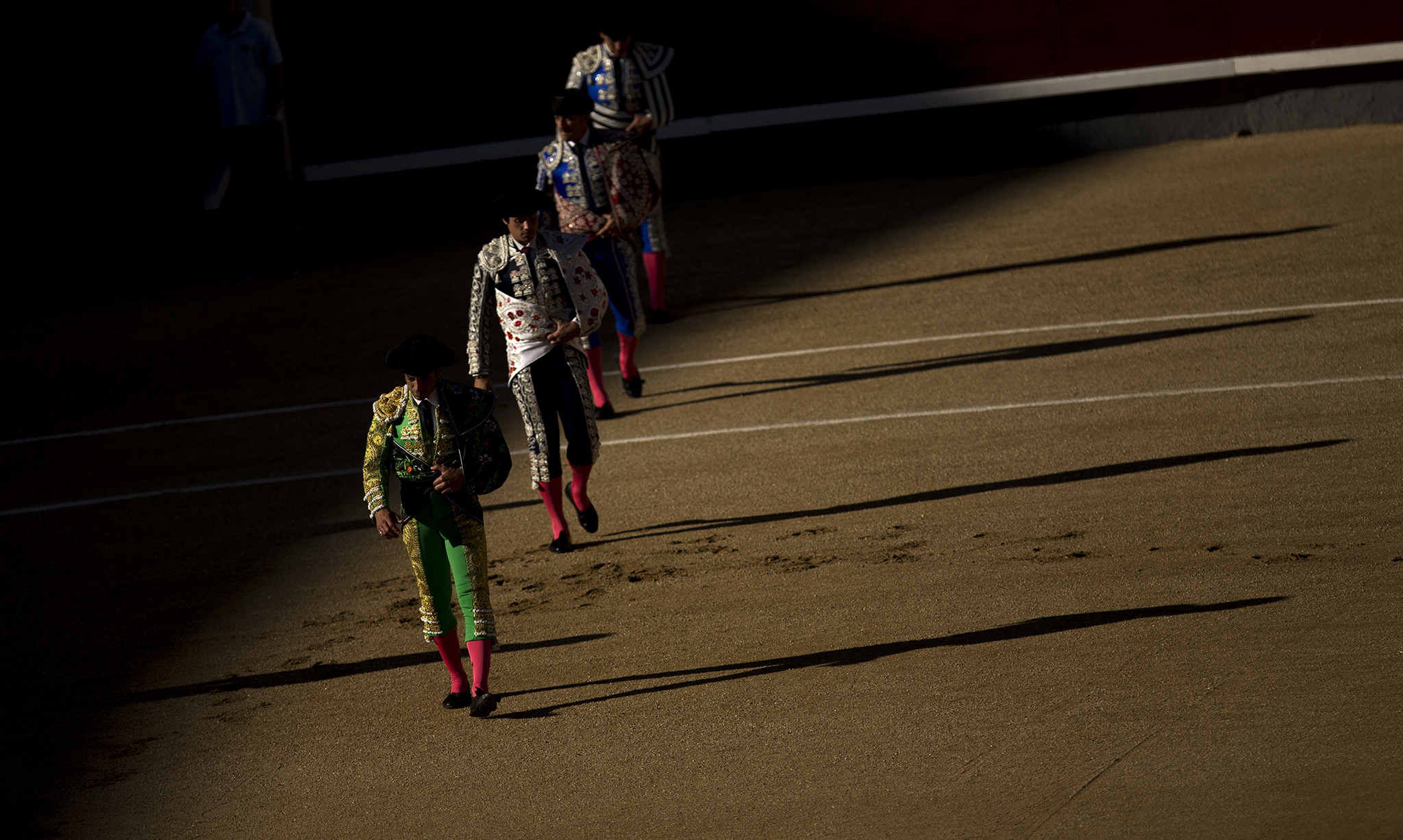 "Bullfighters and assistants walk along the ring during the ""paseillo"" or ritual entrance to the arena prior a bullfight at the Las Ventas bullring in Madrid, Sunday, Aug. 7, 2016. (AP Photo/Francisco Seco)"